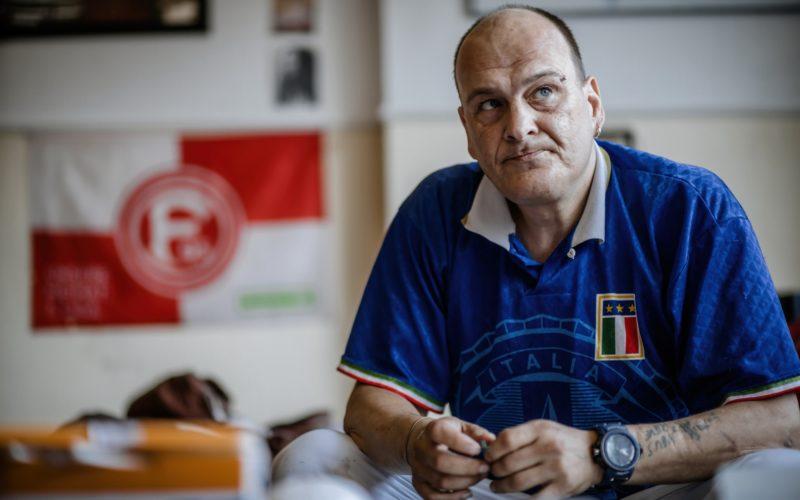 """Andre in seiner Wohnung, die er durch das Projekt """"Housing first"""" bekommen hat. Er ist Fortuna-Sympathisant, sagt er. Dortmund ist aber gut. Foto: Andreas Endermann"""
