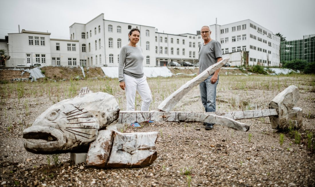Hilli Hassemer und Peter Ripka vor der großen Fischgräte, die neben der ehemalige Liesegang-Fabrik liegt und um die herum im August Blumenkreise blühen. Foto: Andreas Endermann